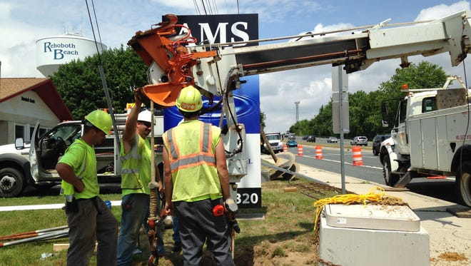Delaware Department of Transportation workers drill a hole for the pole foundation of a 21.5-foot blinking pedestrian sign on the forgotten mile between Rehoboth and Dewey Beach.