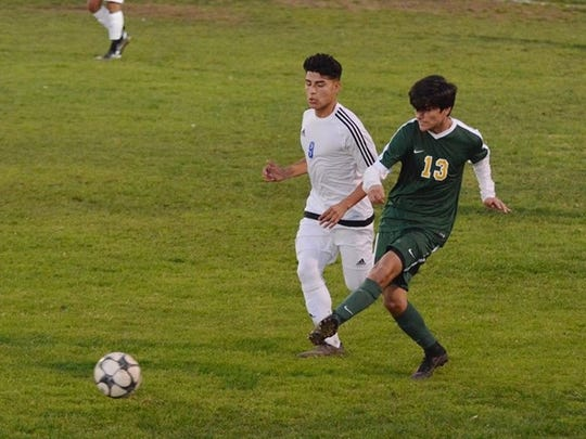 Moorpark High midfielder Ryan Galvez plays a ball forward in the Musketeers' 1-0 win over Channel Islands Tuesday in Oxnard. Channel Islands' Adrian Moreno is marking Galvez.