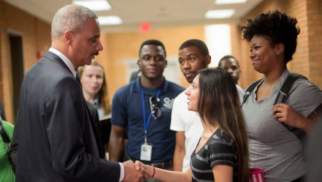 Attorney General Eric Holder shakes hands with Bri Ehsan, 25, after his meeting with students at St. Louis Community College Florissant Valley in Ferguson, Mo., on Aug. 20, 2014. It came nearly two weeks after a white police officer fatally shot 18-year-old Michael Brown.