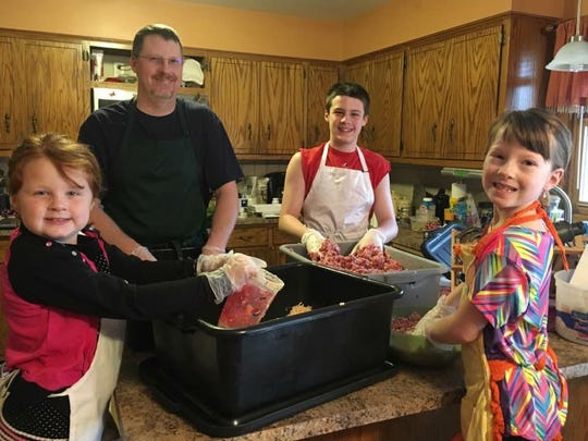 Brad Sagan and his kids, Ella (from left), Kyle and Abby, mix up sausage in the family's kitchen.