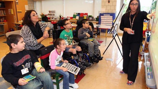 Joseph Juarez, 9, left, teacher Corryn Morris-Pislo, Sofia LaGrippo, 8, Antonio Rodriguez, 9, and Justin Torres Shinzato, 9, listen Oct. 10 as student teacher Stephanie Flannino presents math problems at the Blythedale school.