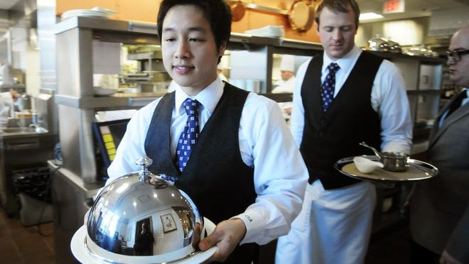 Culinary Institute of America sophomore Joonho Jun carries an entree from the kitchen at the Bocuse restaurant in Hyde Park.