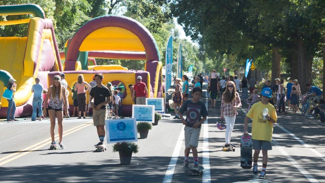 People walk down Remington Street Sunday, September 20, 2015 during Open Streets, an event encouraging people to experience a public street in a way other than driving. Over one mile of Remington Street were filled with music, games and healthy activities.