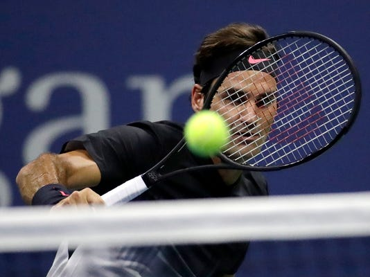 Roger Federer, of Switzerland, returns a shot to Frances Tiafoe, of the United States, during U.S. Open tennis tournament, Tuesday, Aug. 29, 2017, in New York. (AP Photo/Julio Cortez)