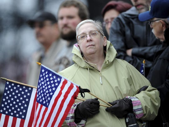 Jocelyn Scalzott-Lammey, from Lower Burrell waits with a crowd for the procession transporting the casket of slain New Kensington Police Officer Brian Shaw at the Rusiewicz Funeral Home in Lower Burrell, Pa., Saturday, Nov. 18, 2017. Shaw was shot in the chest Friday night in New Kensington, northeast of Pittsburgh. The shooting occurred during a foot chase that began shortly after the traffic stop took place. (Pam Panchak/Pittsburgh Post-Gazette via AP)