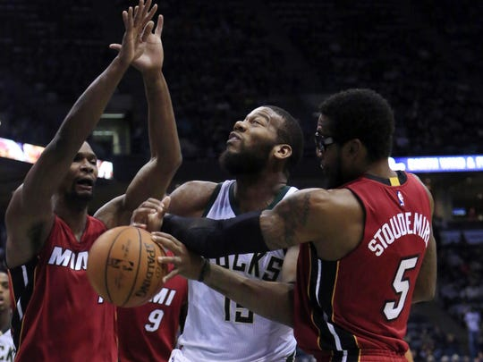 Milwaukee Bucks center Greg Monroe, center, is fouled by Miami Heat forward Amare Stoudemire, right, as Chris Bosh, left looks on during the second half of an NBA basketball game Friday, Jan. 29, 2016, in Milwaukee.
