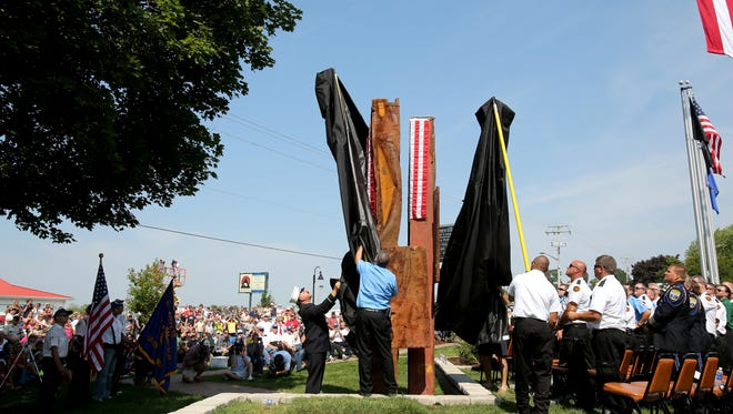 Lt. Joe Torrillo, left, who was a member of the New York Fire Department on 9/11 helps unveil the 9/11 Memorial in Greenville, Wisconsin on Saturday, August 25, 2012. The Memorial features two steel beams from Ground Zero in Manhattan.