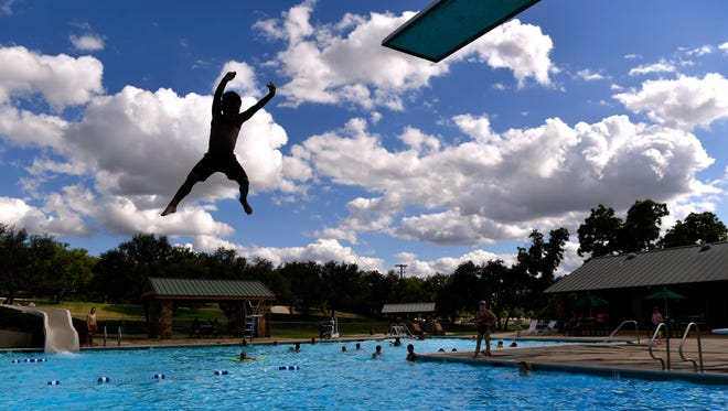 A young swimmer leaps from the high-dive at the Breckenridge Aquatic Park Wednesday. Thursday, the first day of summer, will be hotter than normal, but the real heat (and humidity) arrives over the weekend.