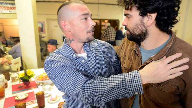 David Webb, left, hugs Haywood Street Congregation Pastor Brian Combs at the Welcome Table lunch in 2014.