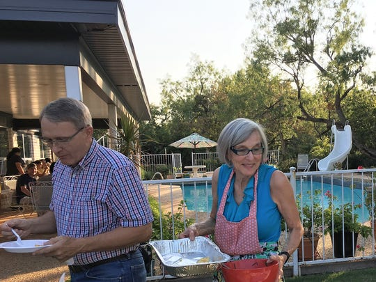 Art and Susan Green clear empty food pans for a serving area outside their northeast Abilene home. For 13 years, the Greens have been hosts to international students attending Abilene Christian University.