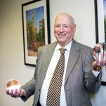 Jim Smith, chief economist at Parsec Financial in downtown Asheville, holds up two of the Crystal Ball awards he's won for economic forecasting. 5/1/15