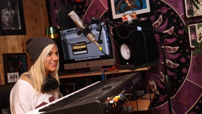 American Idol contestant Jax behind the keyboard in her home recording studio in East Brunswick.