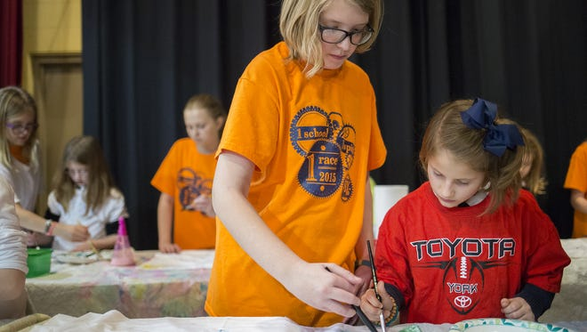 Fifth-grader Megan Fisher, center, and first-grader Isabella Gagliardi decorate a pillowcase at St. Joseph School in Springettsbury Township on Wednesday, Feb. 3, 2016. The pillowcases will be given to children at Children's Home of York and York County Prison, for children of inmates.