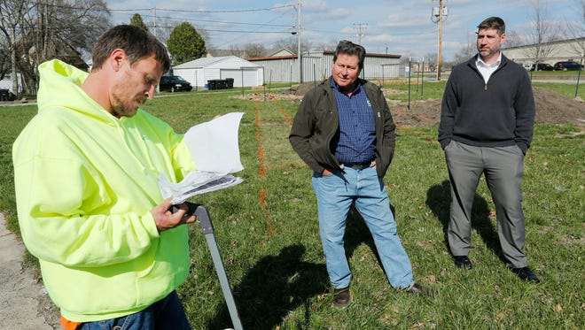 Larry Shelley, left, looks over a map as he meets Ken McCammon, center, and Scott Brown Monday, March 21, 2016, at the community garden at Erie and Cincinnati streets in Lafayette. Shelley, of CC&T Construction, was laying lines around the lot for new sidewalks and curbs. McCammon has plans for community gardens spread out across Lafayette. Bejo Seeds, the company McCammon works for, is donating seeds for the community gardens. McCammon said the community gardens encourage people to get out and meet their neighbors. A wide variety of vegetables will be grown, and McCammon said he hopes that people will help themselves to the fresh produce the community gardens will provide. Brown is co-president of the Historic Jefferson Neighborhood Association.