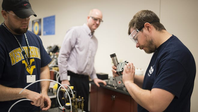 Instructor Kevin Schussler, 36, center, looks on as students Chris Fletcher, 33, left, and Daniel Wallace, 29, work with a pneumatics trainer during class.