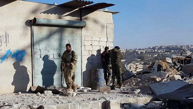 This Sunday, Nov. 27, 2016 photo provided by the Rumaf, a Syrian Kurdish activist group, which has been authenticated based on its contents and other AP reporting, shows Kurdish fighters watch people flee from rebel-held eastern neighborhoods of Aleppo into the Sheikh Maqsoud area that is controlled by Kurdish fighters, Syria.