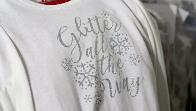 A donated shirt sits on a rack while getting packaged to go to a foster child through A World for Children.
