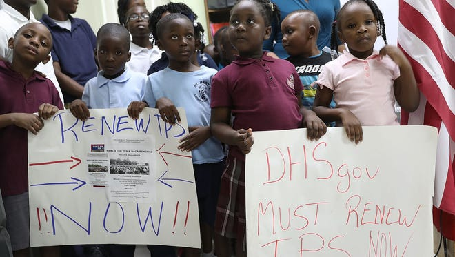 Children hold posters asking the gederal government to renew  Temporary Protected Status during a news conference about the program for people from Haiti, Honduras, Nicaragua and El Salvador at the office of the Haitian Women of Miami in the Little Haiti neighborhood of Miami on Nov. 6, 2017. On Thursday, Jan. 18, 2018, U.S. Citizenship and Immigration Services said current temporary protected status beneficiaries from Haiti now must re-register by March 19, 2018. The move allows them to maintain that status through the program's end in July 2019.