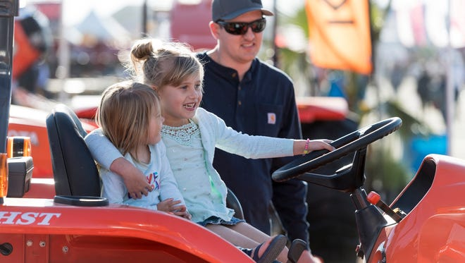 Cody Story of Tulare watches his daughters Cooper Story, 6, and Chandler Story, 2, play behind the wheel of a Kubota 3301 during the World Ag Expo at the International Agri-Center in Tulare on Tuesday, February 13, 2018.
