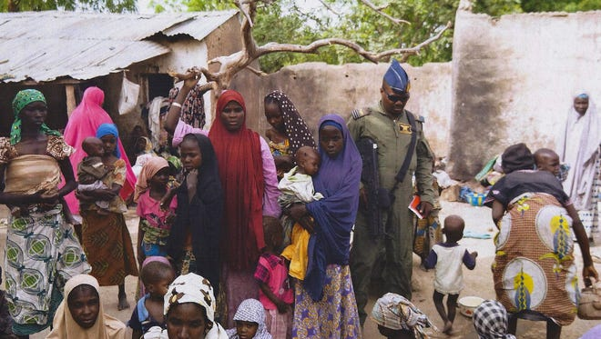 An undated handout picture released by the Nigerian army shows a soldier standing with a group of women and children rescued in an operation against the militant Islamist group Boko Haram.