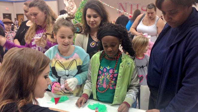 Northwood High junior Kamryn Glenn (front, left) helps fifth-graders Karli Shuler and Price make Grinch crafts Tuesday. Deanna's grandmother Theresa Price (right) and Karli's mother Nekole Shuler (back, center) attended the Christmas-themed parent literacy night  Tuesday.