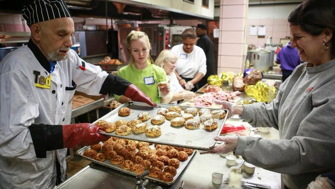 Volunteer Shawna Cooper, right, helps move a tray of cinammon rolls with Ted Loebenberg for the breakfast portion of the annual Wayside Christian Mission Thanksgiving event at the Hotel Louisville. Nov. 27, 2014