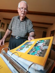 Clyde Hobbs of Anderson looks at a scrapbook from September