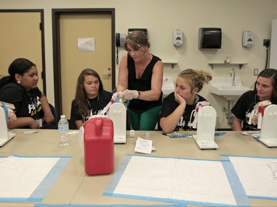 Nursing faculty member Erin Robinson, center, demonstrates how to insert an IV needle into a vein as students look on.