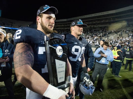 Penn State guard Brian Gaia (12) carries the Big Ten East Division trophy as the team celebrates their 45-12 win over Michigan State in an NCAA college football game in State College, Pa., Saturday Nov. 26, 2016. (Abby Drey/Centre Daily Times via AP)