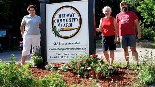 Charles River Bank's Senior Vice President of Customer Care and Relationship Development Ann Sherry, along with Medway Community Farm's Board President Carol Collord and Farm Manger Seth Terramane, pose for a picture with the Farm's new road-side sign on Winthrop Street in Medway.