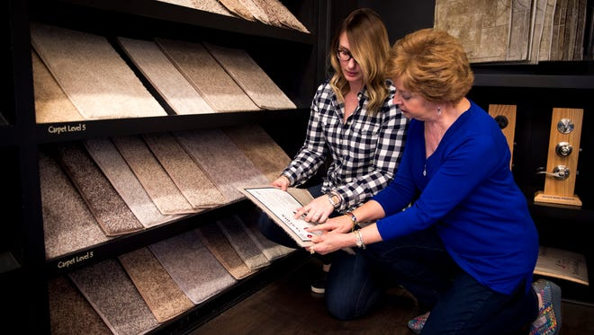 Connie Maynord, right, and her designer Kayla Barnes look over carpet samples at the Goodall Design Center in Nashville last week. Maynord is building a Goodall house.