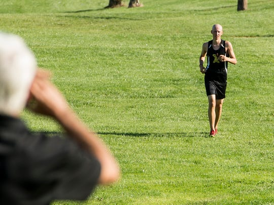 Bob Laudani, left, cheers on his son, Tommy Laudani, as he runs in a cross country meet at Bermudian Springs.
