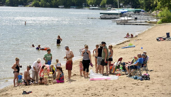 Families enjoy the sunshine and the chance to cool off a bit at Schroeder Regional Park & Campground's beach on Cedar Lake near Annandale. The county park is a popular swimming destination but also offers 51 campsites and other amenities.
