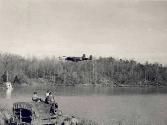 This government photo shows troops scoring a bombing run on Issaqueena Lake. The B-25 traveled between 200 mph and 250 mph at very low altitude and tried to hit a target in the water with practice bombs.