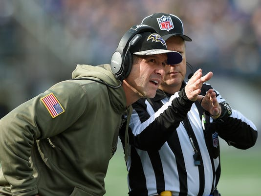 Baltimore Ravens head coach John Harbaugh, left, talks over a call with a referee during the first half of an NFL football game against the Tennessee Titans in Baltimore, Sunday, Nov. 9, 2014. (AP Photo/Nick Wass)