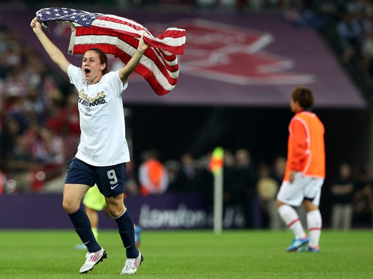 Midfielder Heather O'Reilly celebrates with the American flag after the U.S. women's soccer team  won the gold medal game  in 2012 in London.