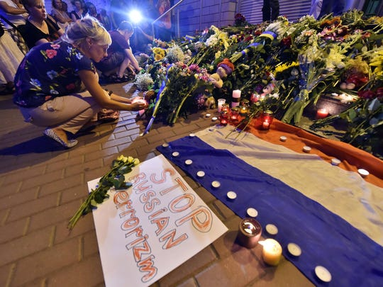 "A woman lights a candle near a placard reading ""Stop Russian terrorism!"" in front of the Embassy of the Netherlands in Kiev on July 17, 2014, to commemorate passengers of Malaysian Airlines flight MH17."