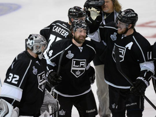 Justin Williams #14 of the Los Angeles Kings celebrates his game-winning goal in overtime with teammates Jonathan Quick #32 and Anze Kopitar #11 after the Kings' 3-2 victory against the New York Rangers during Game 1 of the 2014 NHL Stanley Cup Final at the Staples Center on June 4, 2014 in Los Angeles.