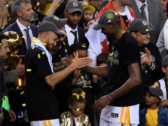 Stephen Curry celebrates with forward Kevin Durant