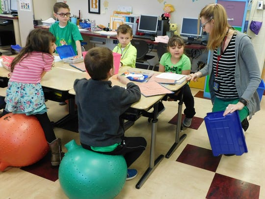 Clyde Elementary School teacher Aubrey Baur kneels while talking to her students and passing out folders.
