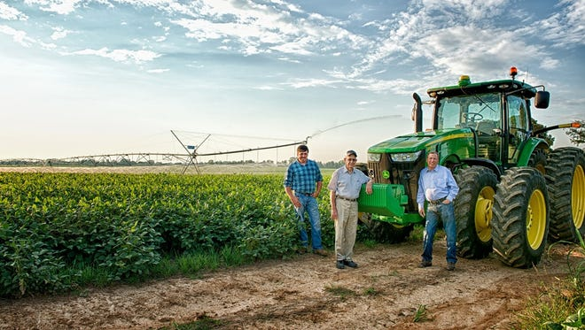Three generations of John Verells farm in partnership in Jackson, Tennessee. The youngest, Johnny (shown left in attached photo), has been named Tennessee Farmer of the Year. The three are shown on their operation, Verell Farms. John Sr. is shown center, and John Jr. is shown on the right.