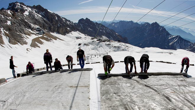 Workers cover a glacier with large plastic sheets on the peak of Germany's highest mountain Zugspitze near Garmisch-Partenkirchen on May 10, 2011. The sheets are meant to keep the glacier from melting during the summer months.
