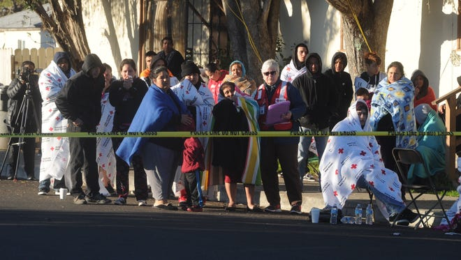 Bystanders outside a Port Hueneme apartment building watch as firefighters wrap up a scene at an apartment building where two people died early Friday.