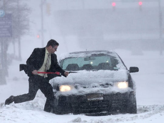 Michael Paul, of Fairport, clears snow from his car in downtown Rochester in the Blizzard of '14.