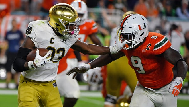 Notre Dame Fighting Irish running back Josh Adams (33) stiff arms Miami Hurricanes defensive lineman Chad Thomas (9) during the first half at Hard Rock Stadium.
