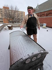 Charlie Koenen, executive director of Beevangelists, checks the winter hive of bees on the roof of Redeemer Lutheran Church on Friday.