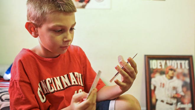 Cory Hansell, a 7-year-old Reds fan from Lawrenceburg, Indiana, shows off ticket stubs from every game he and his family have ever been to.