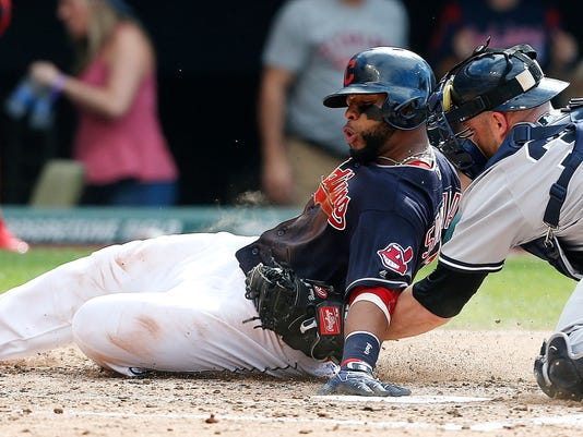 Cleveland Indians' Carlos Santana, left, is tagged out at home plate by New York Yankees' Brian McCann (34) during the third inning of a baseball game Saturday, July 9, 2016, in Cleveland. (AP Photo/Ron Schwane)