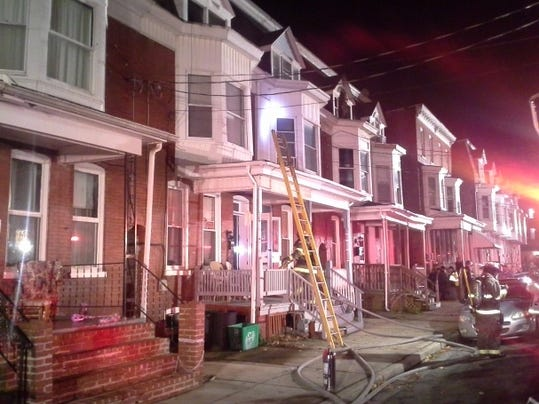 Firefighters work after putting out a blaze that affected two row homes on Smyser Street, York City.