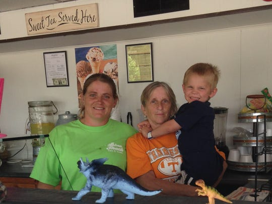 It's a family affair at the Dino Shack. Owner Patricia McMahan holds her grandson, Daniel Gross. At left is her daughter Sarai Gross, who also works at the Powell eatery.